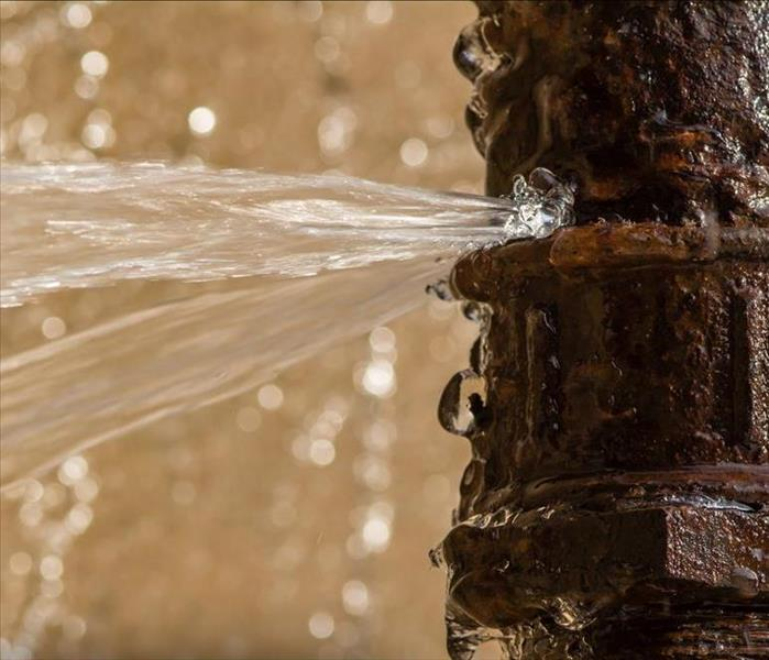 Rusty burst pipe spraying water