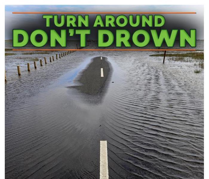 "A flooded street with a sign on top of the picture that say ""Turn around, don't drown"